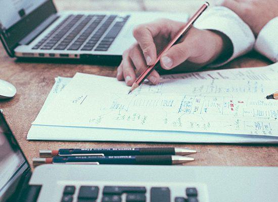 foto con primo piano di due mani che scrivono su un foglio su una scrivania con due laptop aperti