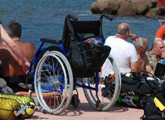 Una foto in un Parco Inclusivo e accessibile con delle persone con disabilità sedute in procinto di entrare in acqua